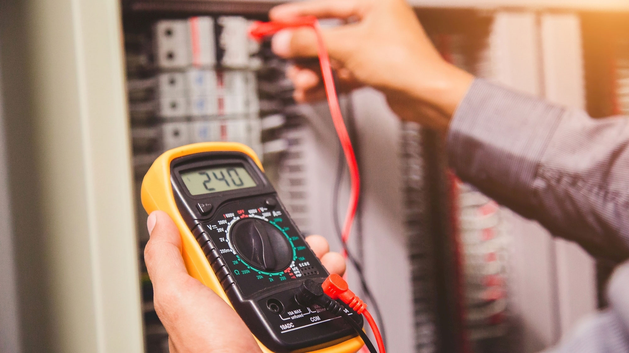 Engineer is measuring voltage or current by voltmeter in control panel